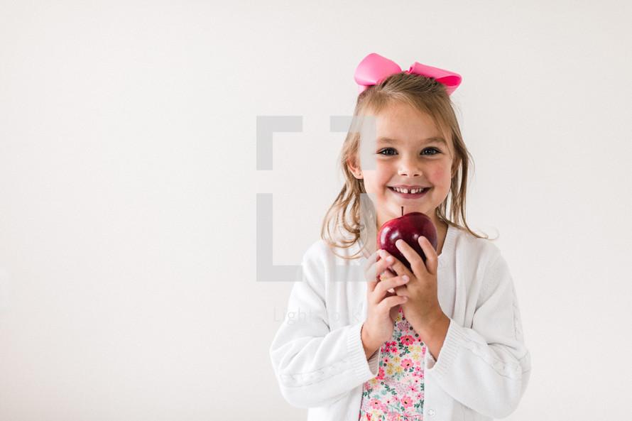 student holding an apple for the teacher