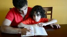 Brothers reading the Bible and praying together.