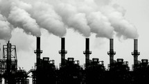 Black and white image of active smokestacks.