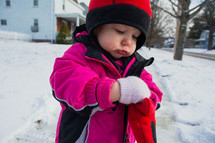 a toddler girl in a winter coat and mittens standing in the snow