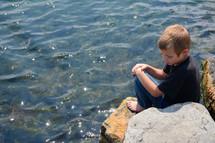 a boy sitting on a rock on a lake shore