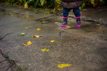 a toddler in rain boots splashing in a puddle