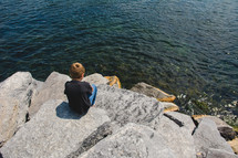 a little boy sitting on a rock along a shore