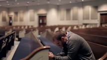 Man praying in the pew.