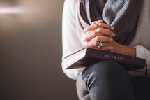 A woman sits with hands clasped on a Bible.