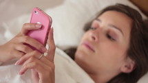 teen girl texting in bed