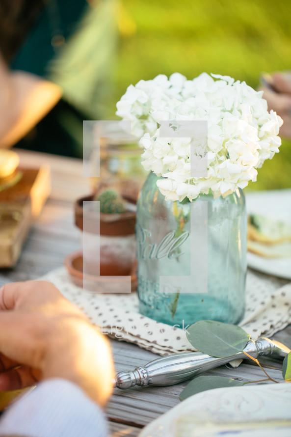 flowers in a mason jar vase on a dinner table