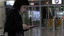 a woman walking through a terminal looking down at a tablet