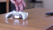 Placing a video game controller on a table and walking away.