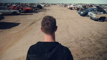 Man walking around looking at cars  at an auto salvage yard.