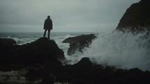 man watching waves crashing into a rocky shore