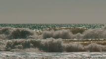 Slow motion ocean waves crashing on to shore.