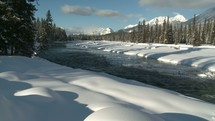 flowing river and snow covered river banks