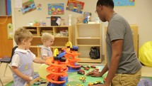 a man and toddlers in a preschool classroom