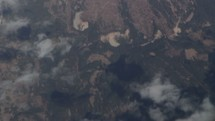 Aerial view of the earth and clouds from a plane flying overhead.