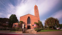 Timelapse of people entering  a church on Sunday morning with clouds moving in the sky overhead.
