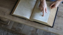 Aerial view of hands flipping the pages of a Bible.