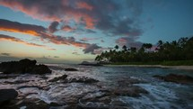 Timelaspe video on a beach in Ko-Olina on the Hawaii island of Oahu.  This tropical time-lapse shows a beautiful sunset of clouds while ocean waves hit the rocks and sand.