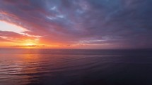 Timelapse of the sun setting over the ocean on a cloudy day as night falls.