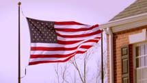 An American Flag outside a red brick building, waving in the wind