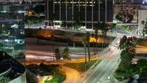 Timelapse of city downtown at night with traffic moving on freeway interchange and surface streets.
