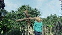 Woman praying at a wooden cross in a garden.