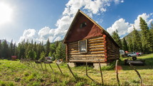 Timelapse of cloud movement over a log cabin in the wilderness.