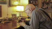 elderly man using a magnifying glass to text on a cellphone