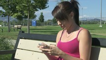 Texting on a smart phone while sitting on a park bench.