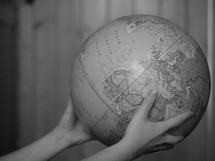 hands holding out a globe