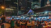 busy outdoor seating area at a Restaurant in Singapore at night