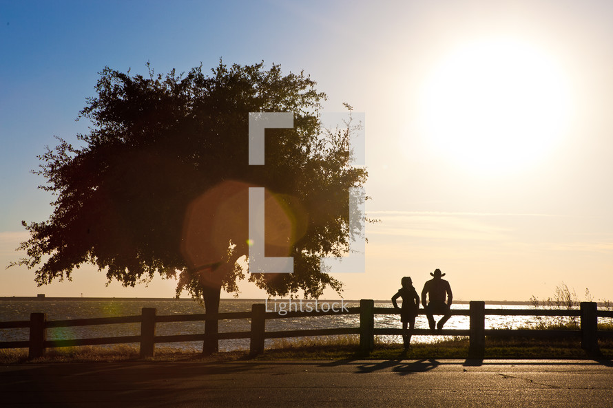 A couple sits on a fence at the edge of a lake at sunset