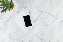 houseplant, cellphone, clips, and paper on marble countertop