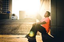 a man sitting on a curb waiting