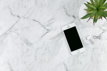 houseplant, cellphone on marble countertop