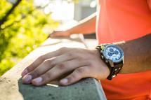 man's hand on a railing and a wrist watch