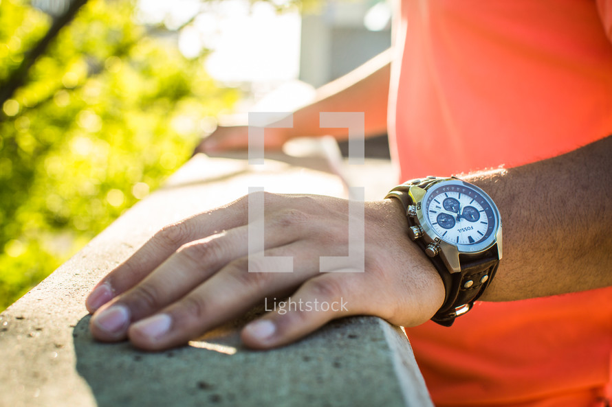 man's hand on a railing and a wrist watch
