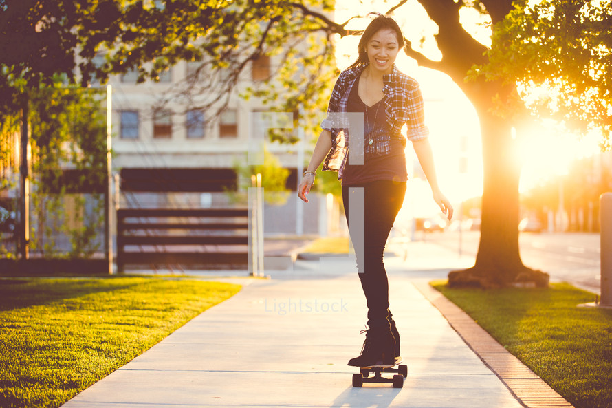 a young woman skating on a skateboard down a sidewalk