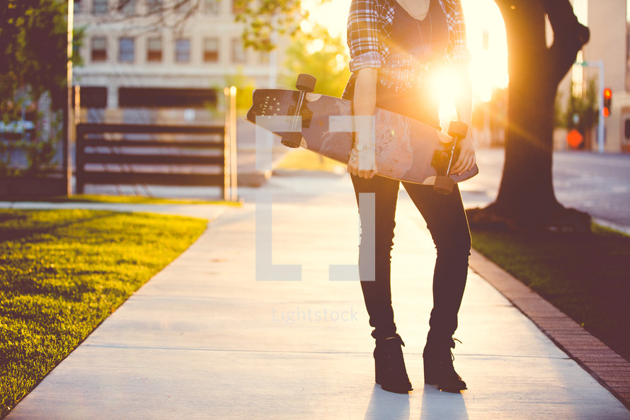 a young woman standing on a sidewalk holding a skateboard