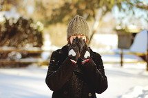 woman standing in snow hiding her face