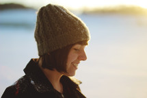woman in a beanie standing outdoors in snow
