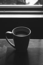 coffee mug in a window sill