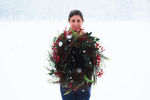 a woman standing in the snow holding a Christmas wreath