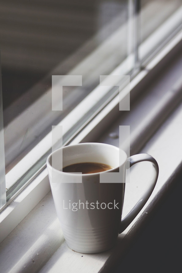 coffee mug in a window sill