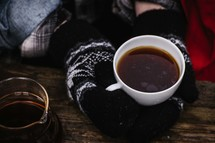 hands in mittens holding a coffee cup