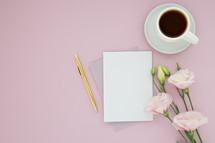 A blank notecard, gold pen, cup of coffee and pink flowers on a pink background.