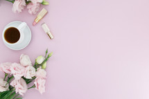 Pink flowers, cup of coffee and lipstick on a pink background.