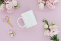 A white coffee cup on a pink background surrounded by pink flowers.