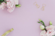 gold clips and tape, and pink flowers on a pink background