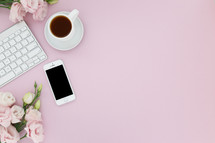 Computer keyboard, cellphone, cup of coffee and pink flowers on a pink background.